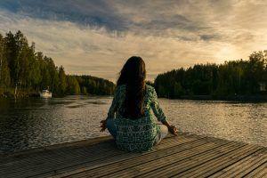 Chica meditando al borde de un lago